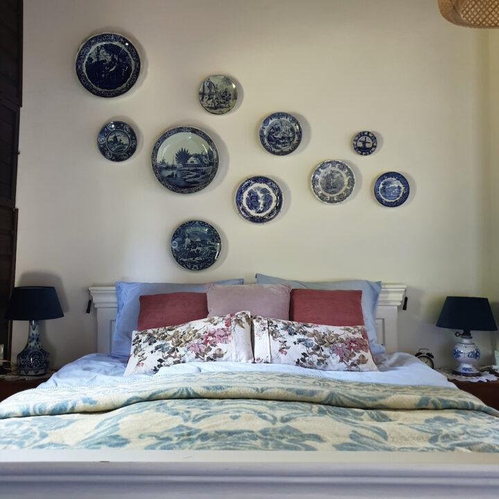 Slaapkamer met porseleinen bordjes boven het bed