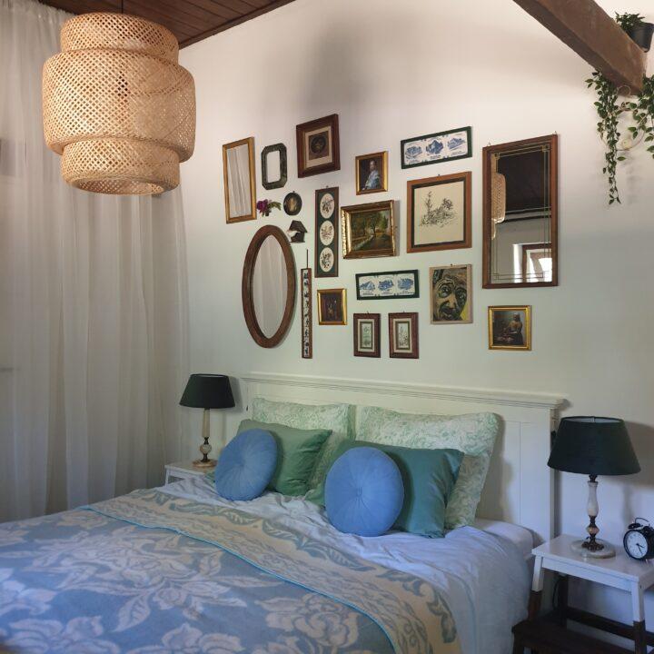 tweepersoons bed met een verzameling fotolijstjes erboven