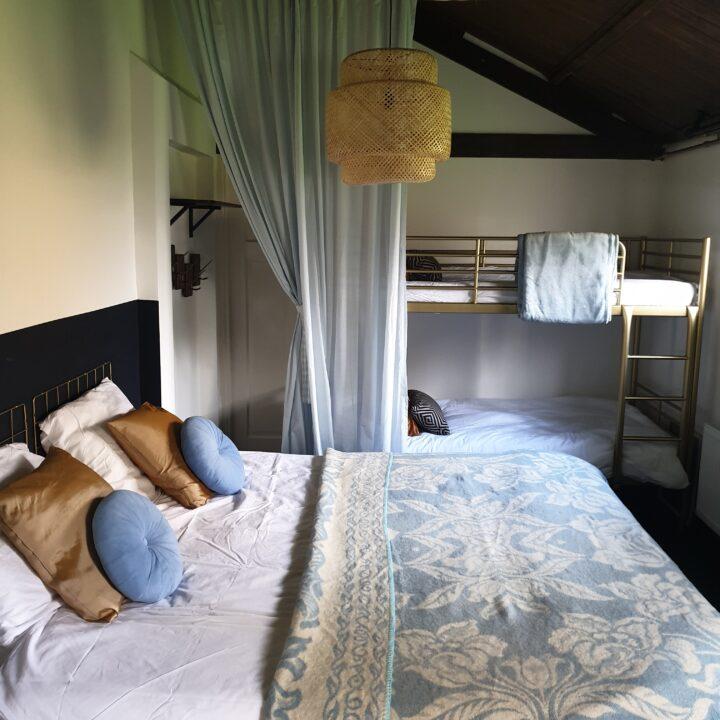 Slaapkamer met tweepersoons bed en stapelbed in groot vakantiehuis