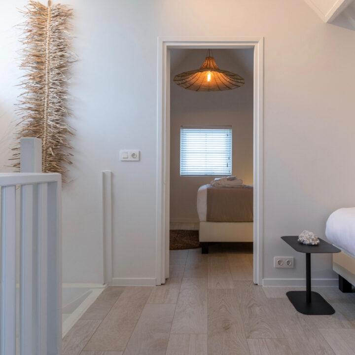 Slaapkamer met tweepersoonsbed en een extra bed op de overloop in het vakantiehuis in Zeeland