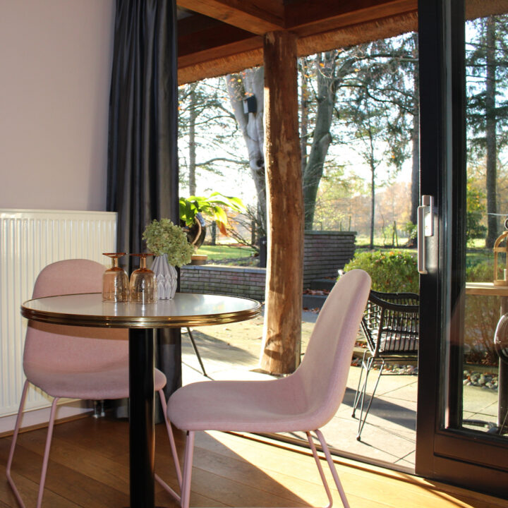 Tafeltje met roze fauteuils voor openslaande tuindeuren