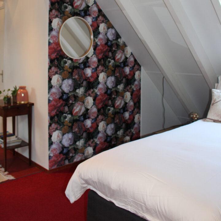Slaapkamer met bloemenbehang in de B&B
