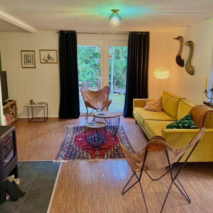 Woonkamer met warme kleuren in het boshuisje, met een houtkachel