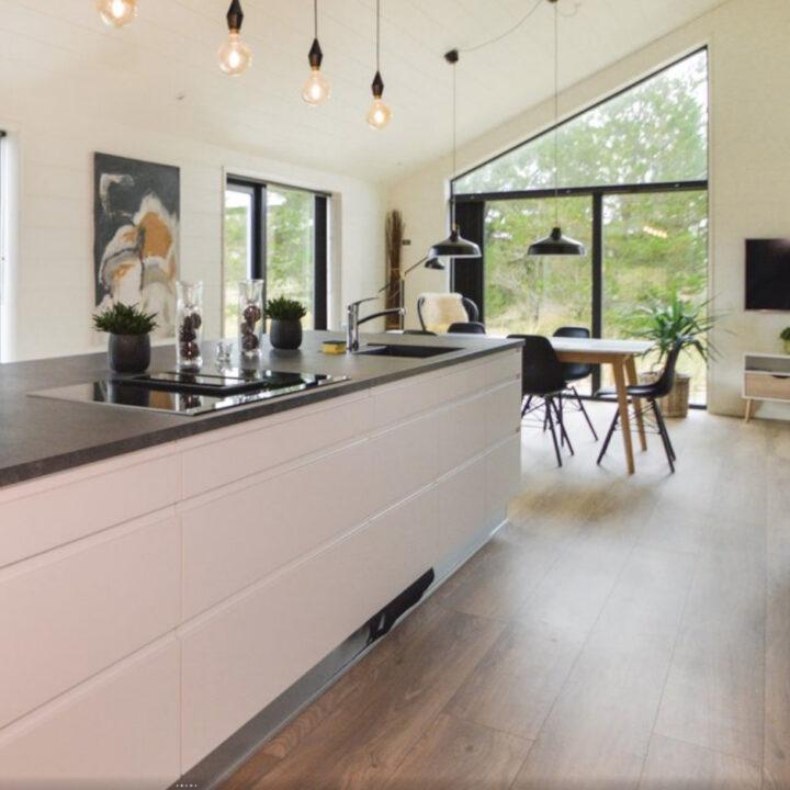 Moderne keuken met kookeiland en 6-persoons eettafel op de achtergrond