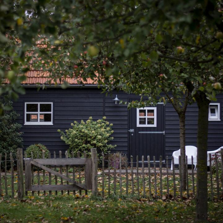 Zwart houten huisje voor twee personen met twee witte stoeltjes