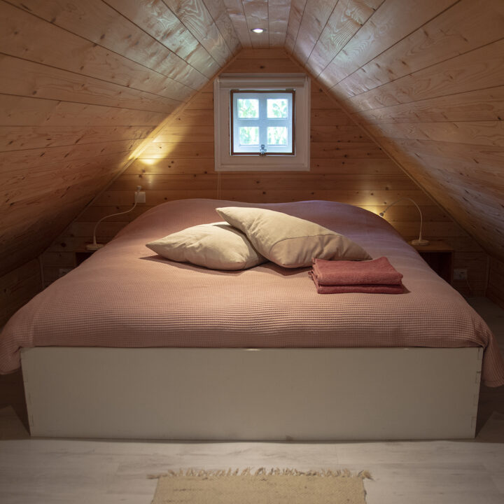 Tweepersoons bed op de vide van het knusse huisje