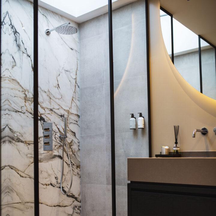 Badkamer met dubbele regendouche met glazen dak erboven