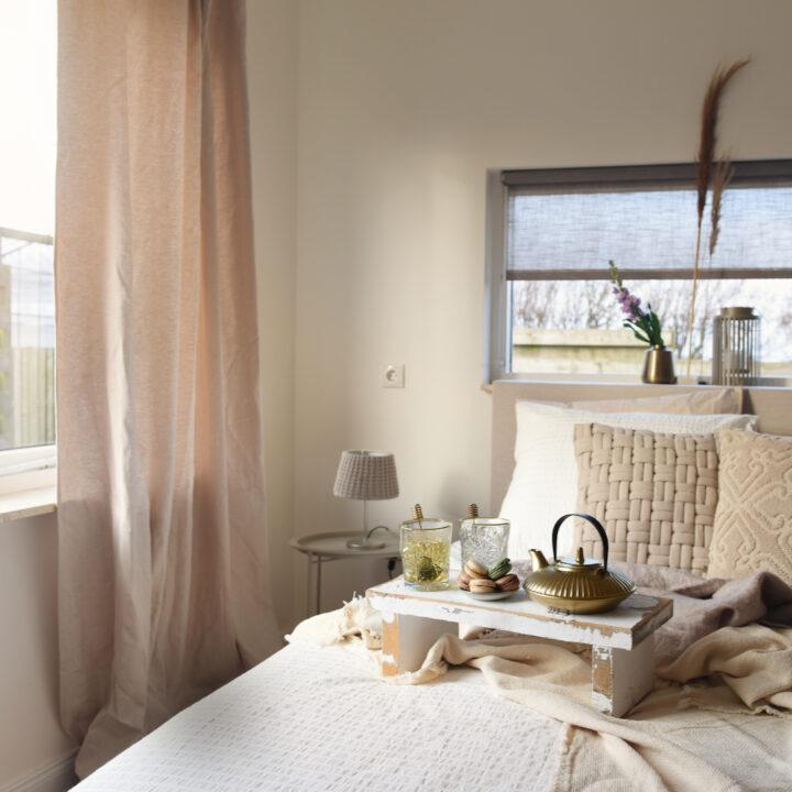 Vakantiehuis slaapkamer met thee op bed