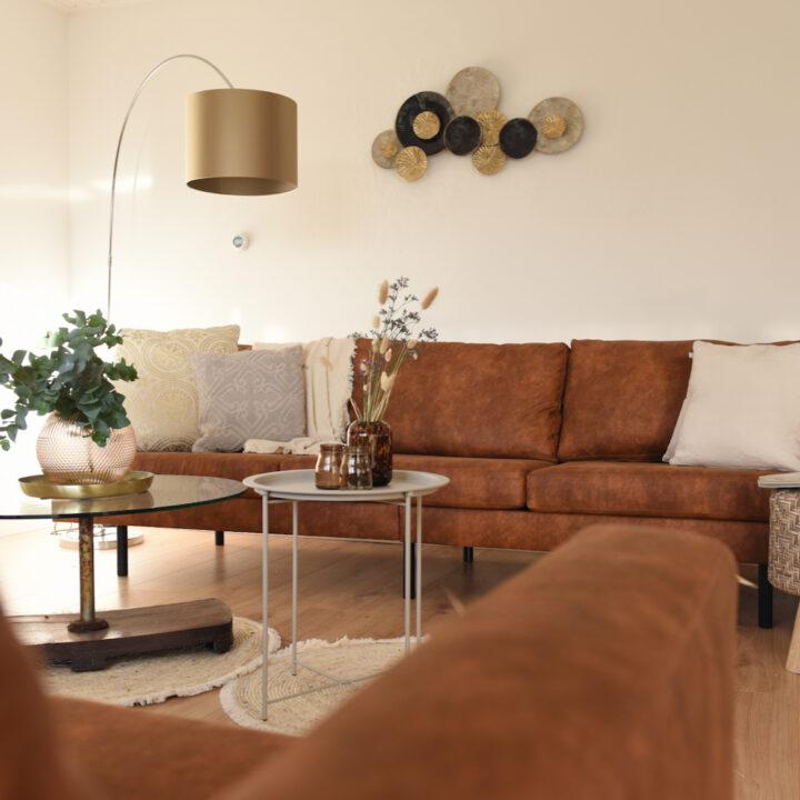 Zithoek met bruine bank en ronde tafels in het vakantiehuis