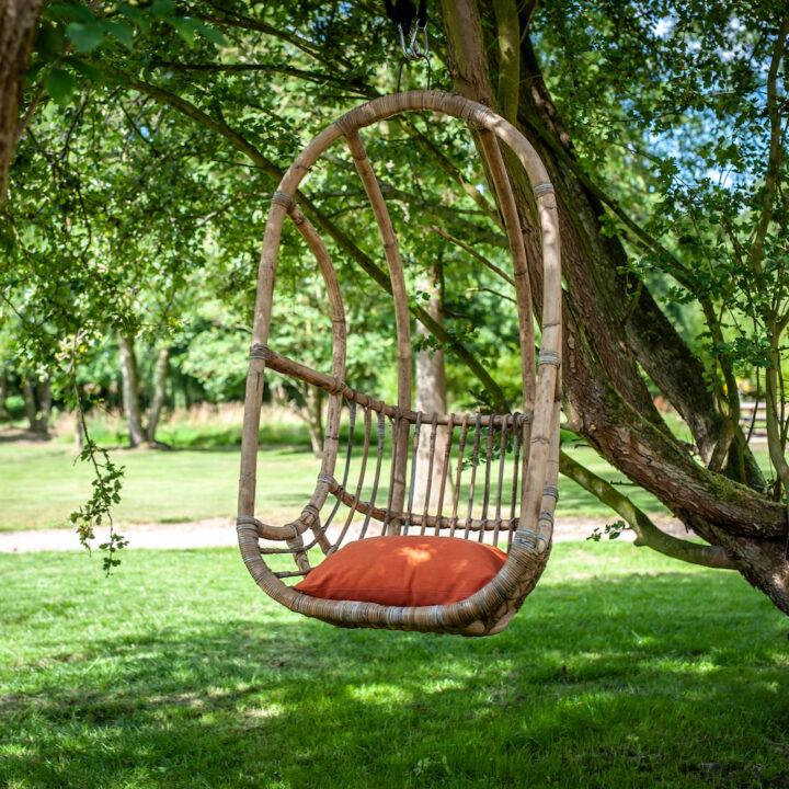 Hangstoel met rood kussentje in de tuin van de Steurshoeve