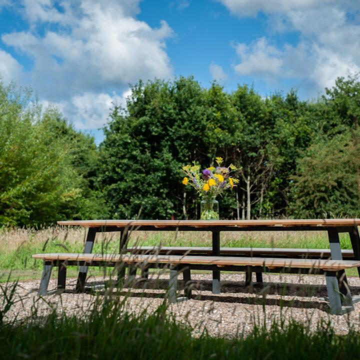 Lange picknicktafel met veldboeket